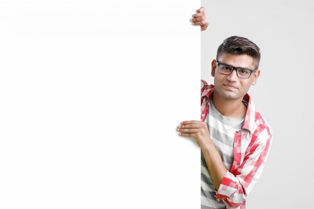 Hübscher indischer asiatischer männlicher student, der leeres schild zeigt