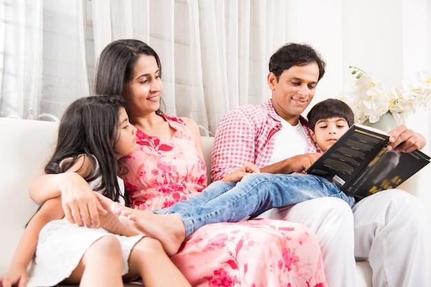 Hübscher indischer asiatischer vater oder hübsche mutter, die ein buch für kinder liest, während sie zu hause über dem sofa sitzt