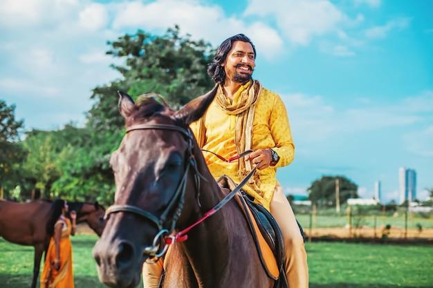 Hübscher indischer bärtiger indischer mann, der ein pferd in einem reitverein reitet