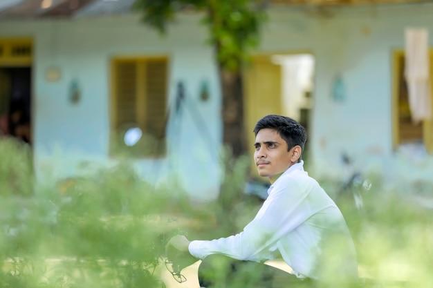 Hübscher indischer junge, der weißes hemd trägt