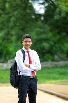 Hübscher indischer junge, der weißes hemd und rote krawatte trägt