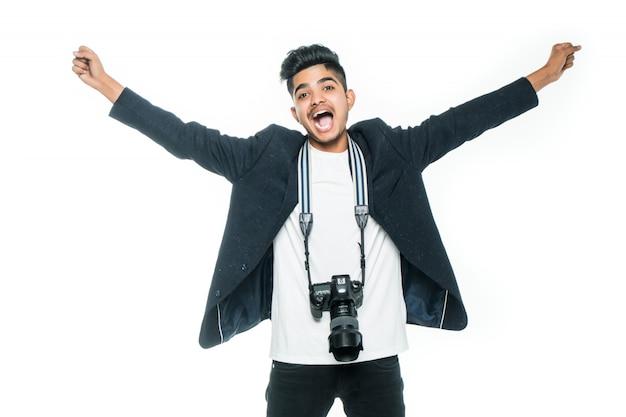 Hübscher indischer junger mann mit einer kamera mit erhöhten händen auf weißem hintergrund