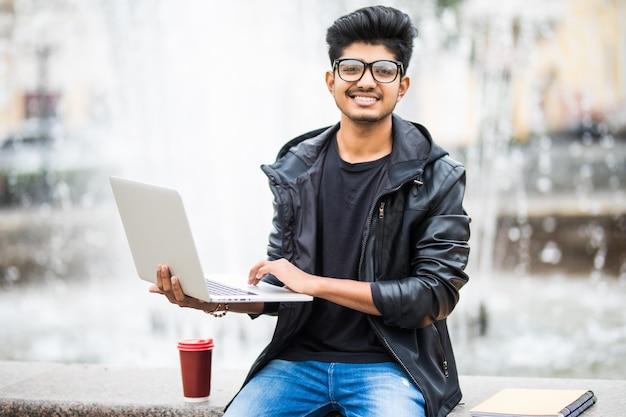 Hübscher indischer mann mit laptop beim sitzen nahe dem brunnen im stadtzentrum an einem tag