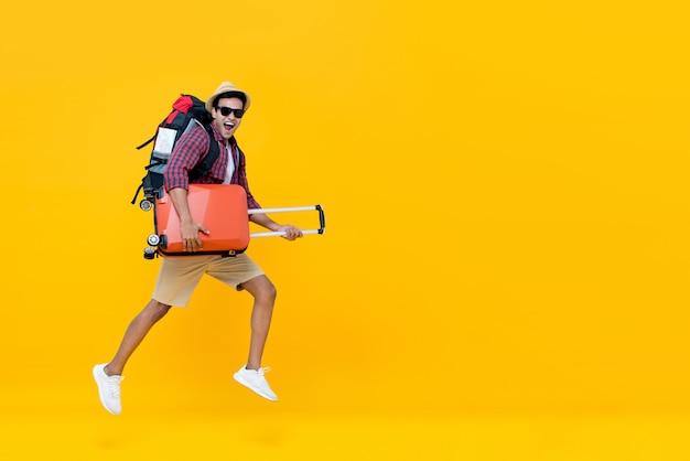 Hübscher indischer touristischer mann mit dem rucksack, der gepäck und das springen hält
