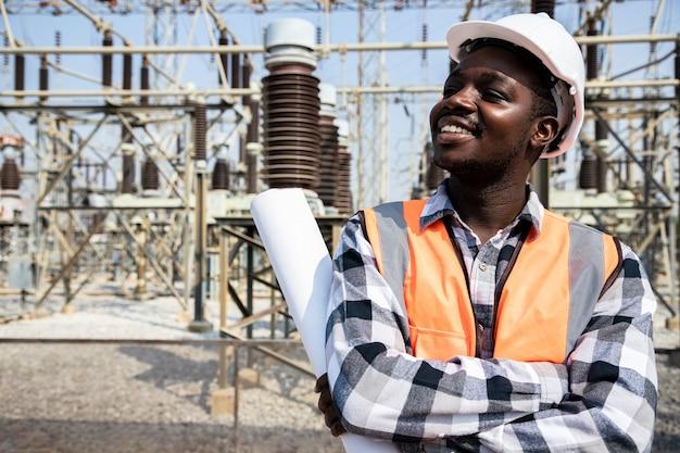 Hübscher ingenieurmann, der papierprojekte hält, plant und trägt helm vor hochleistungskraftwerk. rückansicht des auftragnehmers auf hintergrund von kraftwerksgebäuden.
