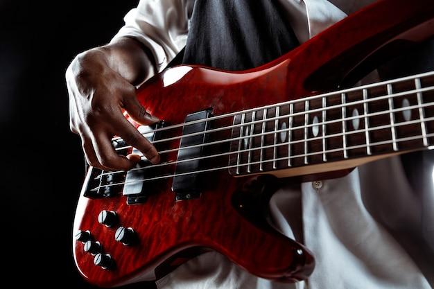 Hübscher jazzmusiker der afroamerikaner, der bassgitarre im studio auf einem schwarzen hintergrund spielt. musikkonzept. junger freudiger attraktiver kerl, der improvisiert. nahaufnahme retro-porträt.