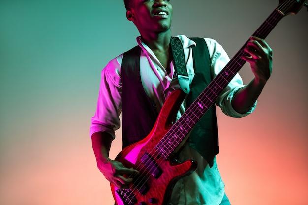 Hübscher jazzmusiker des afroamerikaners, der bassgitarre im studio auf einem neonhintergrund spielt. musikkonzept. junger freudiger attraktiver kerl, der improvisiert. nahaufnahme retro-porträt.