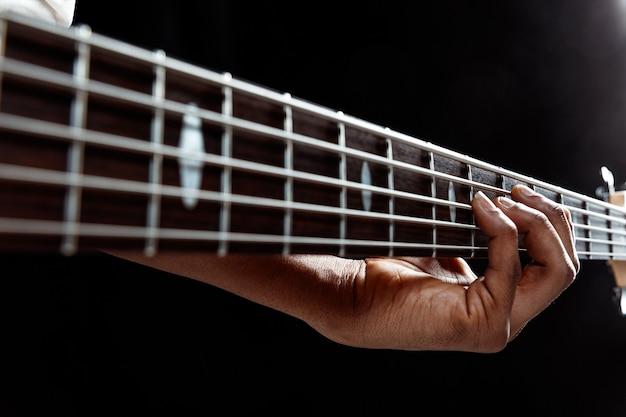 Hübscher jazzmusiker des afroamerikaners, der bassgitarre im studio auf einem schwarzen hintergrund spielt. musikkonzept. junger freudiger attraktiver kerl, der improvisiert. nahaufnahme retro-porträt.