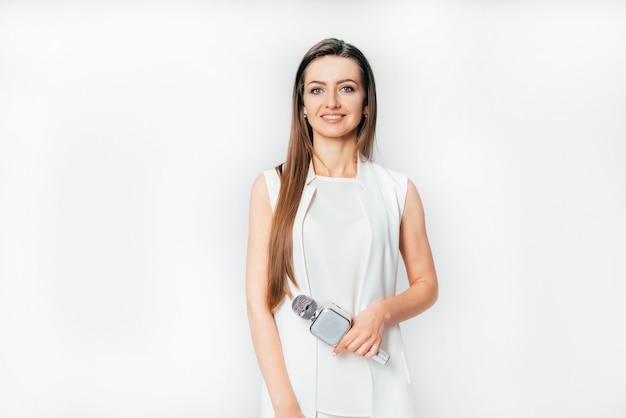 Hübscher journalist in einem weißen anzug steht mit einem mikrofon in der hand
