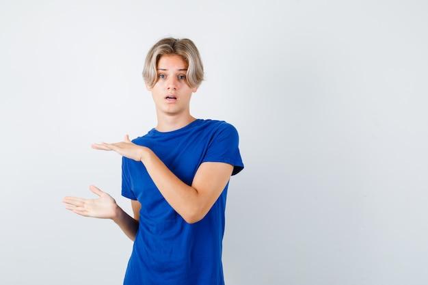 Hübscher jugendlich junge, der größenschild im blauen t-shirt zeigt und verwirrt schaut. vorderansicht.
