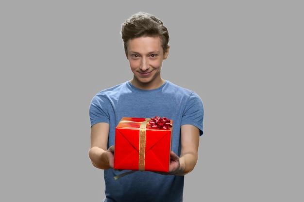Hübscher jugendlich junge, der jemandem geschenkbox anbietet. kaukasischer kerl, der geschenkbox zur kamera steht, die gegen grauen hintergrund steht.