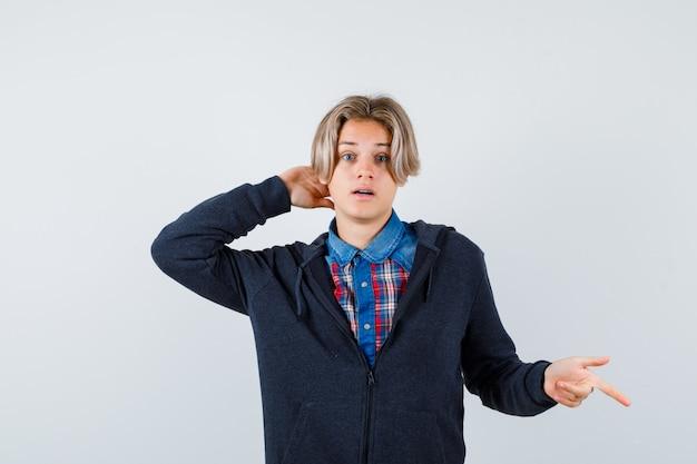 Hübscher jugendlicher junge, der nach unten zeigt, mit der hand hinter dem kopf im hemd, im hoodie und verwirrt schauend. vorderansicht.