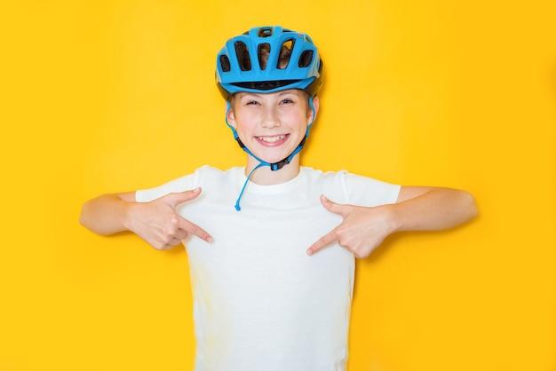 Hübscher jugendlicher junge, der radfahrersicherheitshelm über lokalisiertem gelbem hintergrund trägt. gewinnerkonzept