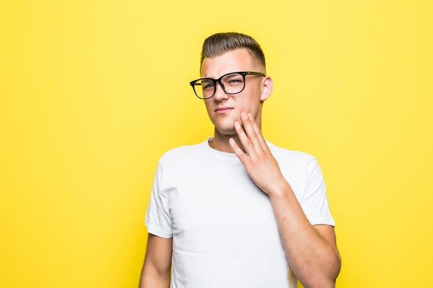 Hübscher junge berührt sein gesicht, gekleidet in weißes t-shirt und transparente brille, die auf gelb isoliert werden