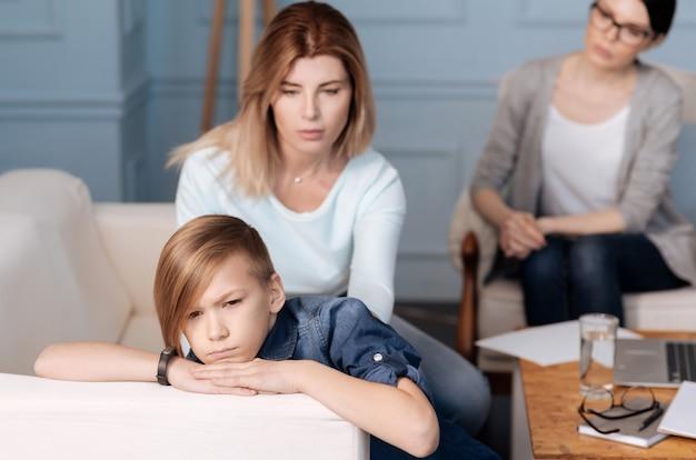 Hübscher junge, der jeans kostüm trägt, das stilvollen haarschnitt hält hände auf weißem rücken des sofas hält, während von mutter abwendet