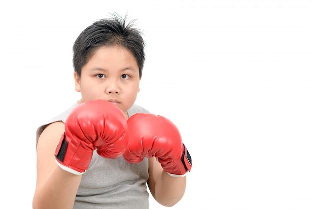 Hübscher junge, der mit roten boxhandschuhen kämpft
