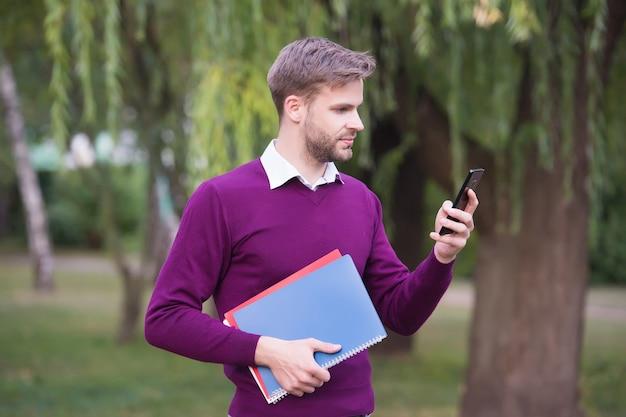 Hübscher junge, der telefon zum lernen und lesen von elektronischen büchern, technologie verwendet.