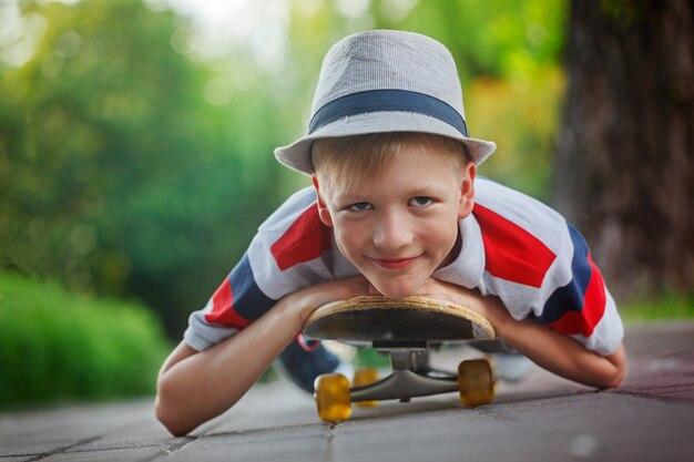 Hübscher junge des nahaufnahmeporträts im hut, der auf skateboard am sommertag liegt