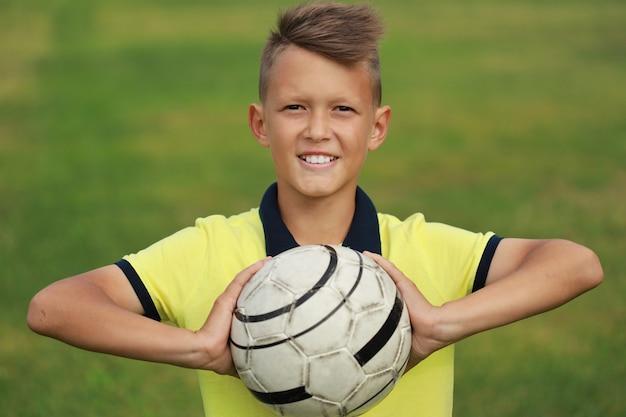 Hübscher junge fußballspieler in einem gelben t-shirt auf einem fußball hält den ball in seinen händen