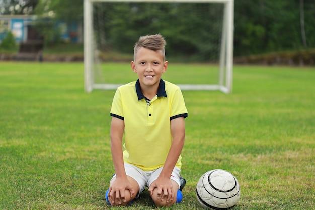 Hübscher junge fußballspieler in einem gelben t-shirt sitzt auf dem fußballplatz