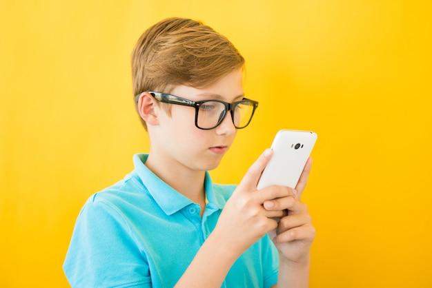 Hübscher junge in den gläsern spielt tablette. das konzept der sehschwäche, schaden von geräten, kurzsichtigkeit