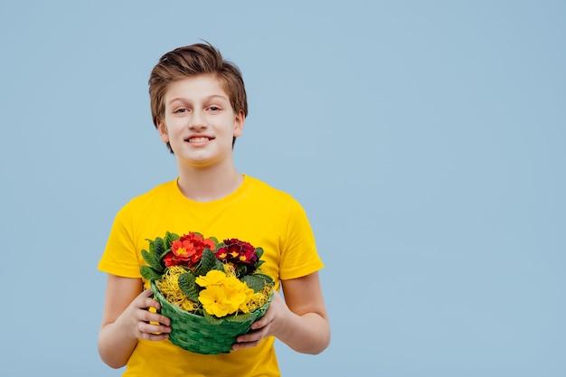 Hübscher junge mit blumenkorb in seiner hand, im gelben t-shirt lokalisiert auf blauer wand, kopienraum
