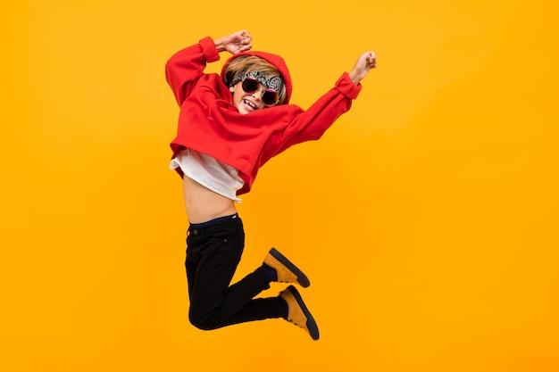 Hübscher junge mit einem kopftuch auf dem kopf in einem roten kapuzenpulli mit brille springt auf isoliertes orange