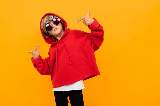 Hübscher junge mit einem kopftuch auf seinem kopf in einem roten kapuzenpulli mit brille, die auf isoliertem orange aufwirft