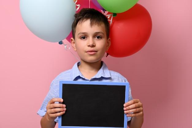 Hübscher junge mit leerer tafel in der hand, der gegen bunte ballons auf rosafarbenem hintergrund mit kopienraum steht