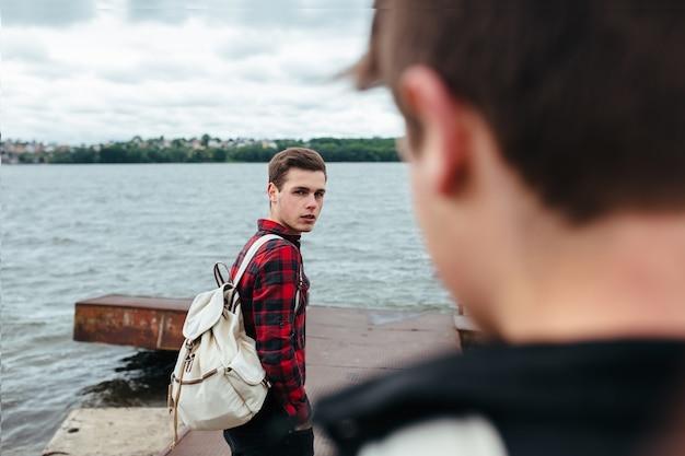 Hübscher junge mit rucksack posieren