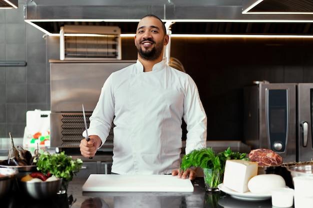 Hübscher junger afrikanischer koch, der in der professionellen küche im restaurant steht, das eine mahlzeit des fleisches und des käsegemüses vorbereitet. porträt des mannes in der kochuniform. konzept für gesunde ernährung.