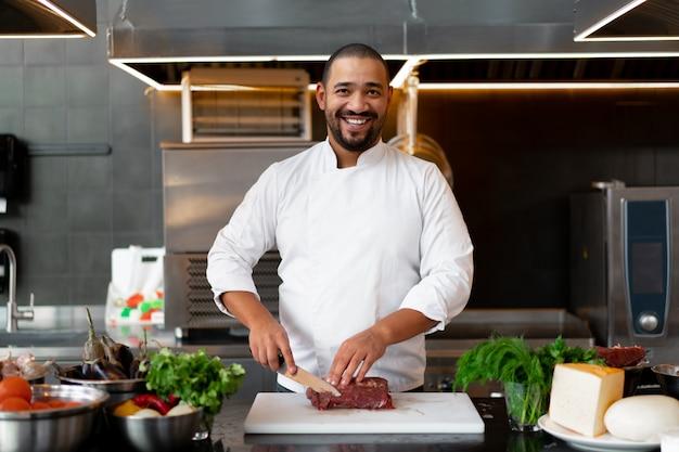 Hübscher junger afrikanischer koch, der in der professionellen küche im restaurant steht, das eine mahlzeit des fleisches und des käsegemüses vorbereitet. porträt des mannes in der kochuniform schneidet fleisch mit einem metallmesser.