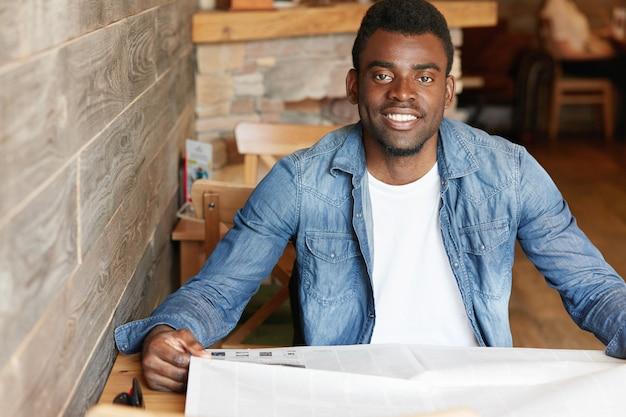 Hübscher junger afrikanischer mann, der jeansjacke über weißem t-shirt trägt, sitzt am gemütlichen café, hält zeitung, liest weltnachrichten