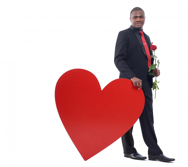 Hübscher junger afrikanischer mann, der rote rose hält