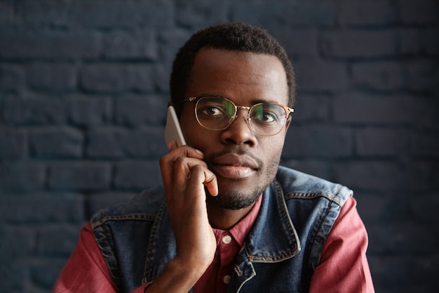Hübscher junger afrikanischer mann, der stilvolle brillen trägt, die auf handy mit seiner freundin sprechen und auf sie warten