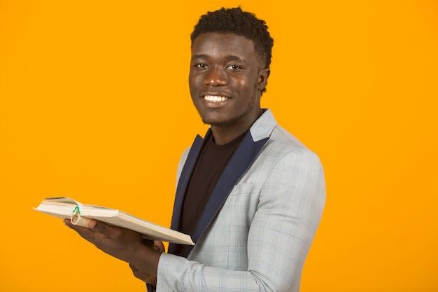 Hübscher junger afrikanischer mann in einer jacke, die ein buch liest