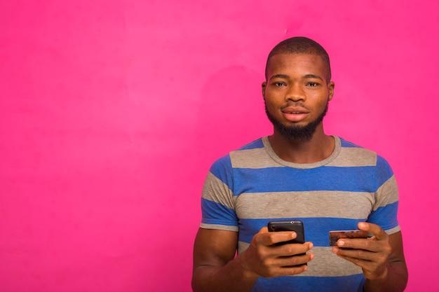 Hübscher junger afrikanischer mann isoliert auf rosa hintergrund, der seine kreditkarte und sein smartphone hält