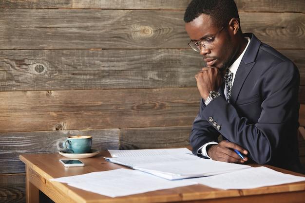 Hübscher junger afrikanischer unternehmer, der einen vertrag liest, bevor er ihn unterschreibt