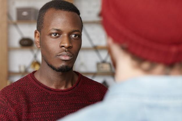 Hübscher junger afroamerikaner, der lässigen pullover trägt, der mit seinem nicht erkennbaren kaukasischen freund spricht und ihm mit interesse und aufmerksamkeit zuhört. selektiver fokus auf das gesicht des schwarzen