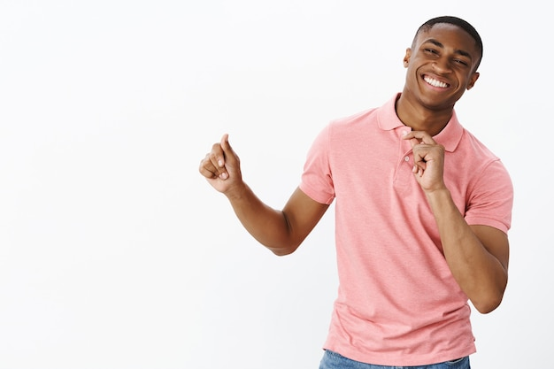 Hübscher junger afroamerikaner mit rosa polo-t-shirt