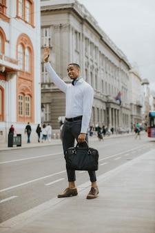 Hübscher junger afroamerikanischer geschäftsmann, der ein taxi auf einer straße wartet?