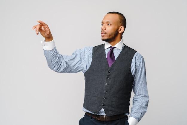 Hübscher junger afroamerikanischer geschäftsmann, der seinen finger auf virtuellen bildschirm zeigt.