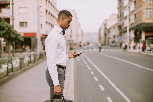 Hübscher junger afroamerikanischer geschäftsmann mit einem handy auf einer straße