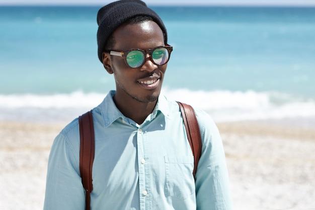 Hübscher junger afroamerikanischer hipster, der entlang der küste geht, gutes wetter und meerblick bewundert und mit dem rücken zum weiten azurblauen ozean steht