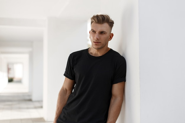 Hübscher junger amerikanischer stilvoller mann mit frisur im schwarzen hemd der mode, das nahe weißer wand steht