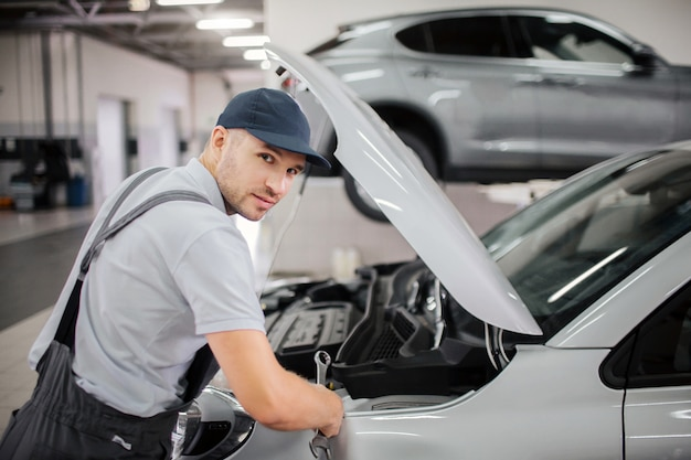 Hübscher junger arbeiter schaut vor der kamera. er macht reparaturen an der vorderseite des autos. guy trägt mütze und uniform.