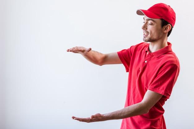 Hübscher junger arbeitnehmer im roten t-shirt. exemplar