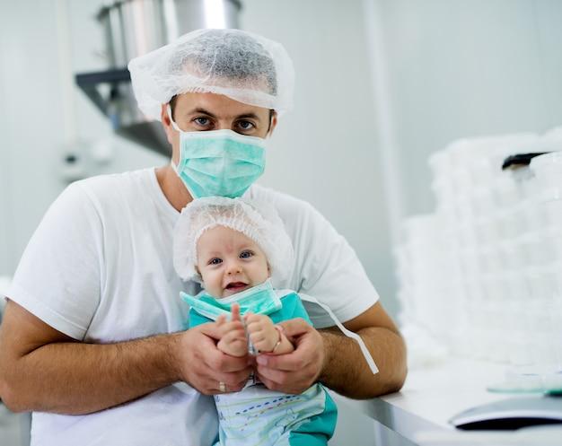 Hübscher junger arzt mit gesichtsmaske, die herrlichen kleinen patienten hält und die kamera betrachtet.