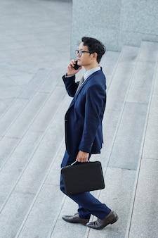 Hübscher junger asiatischer geschäftsmann mit aktentasche, die draußen geht und am telefon anruft