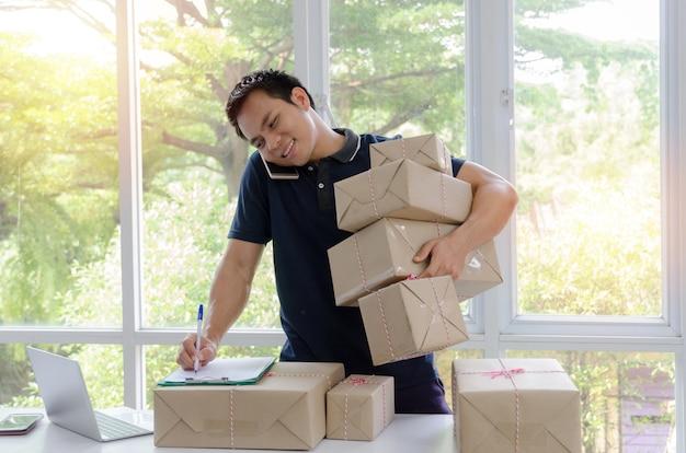 Hübscher junger asiatischer lieferbote glücklich nach neuer bestellung vom kunden